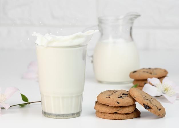 Copo cheio de leite fresco com respingos em uma mesa branca, café da manhã saudável