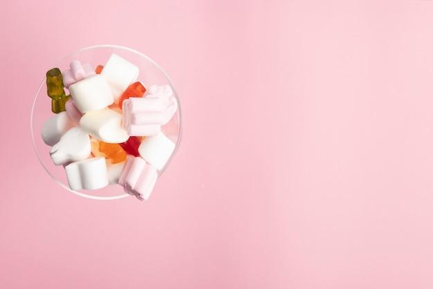 Copo cheio de nuvens de açúcar e ursinhos no fundo rosa