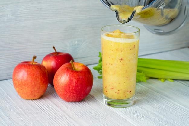 Copo cheio de smoothie feito de maçãs e aipo derramado fora do processador de alimentos
