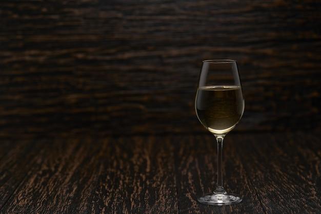 Copo cheio de vinho branco em uma mesa de madeira preta, com espaço de cópia.