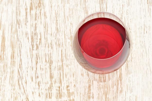 Copo cheio de vinho tinto em uma mesa de madeira branca, ângulo superior.
