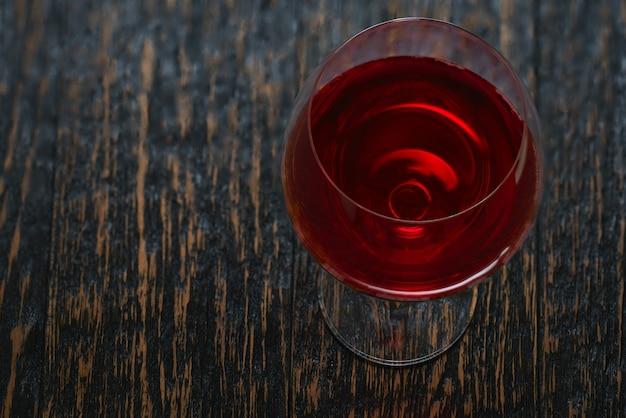 Copo cheio de vinho tinto em uma mesa de madeira preta, ângulo superior.