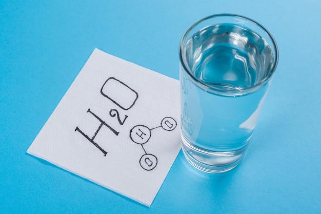 Copo com água, guardanapo com fórmula de água, mesa azul