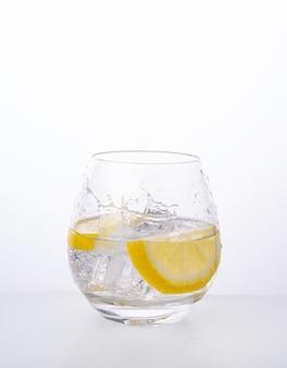 Copo com água mineral com limão e respingos