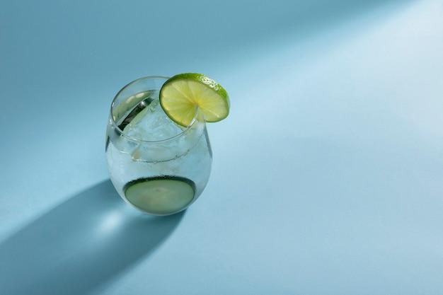 Copo com água mineral e gelo com rodelas de pepino e limão em um fundo azul