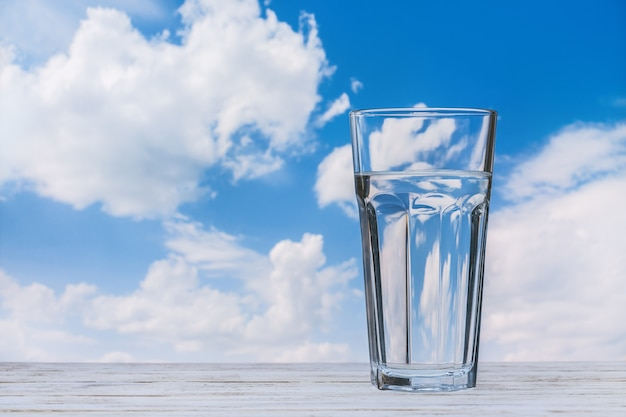 Copo com água na mesa de madeira. céu azul com nuvens brancas. copie o espaço.