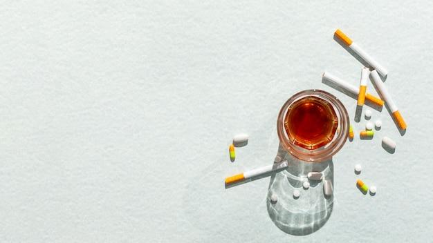Copo com álcool e cigarros
