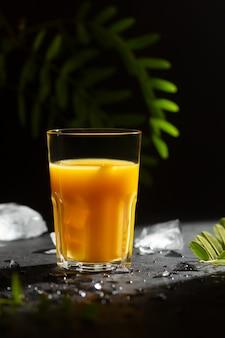 Copo com bebida cítrica não alcoólica refrescante em fundo escuro com gelo e folhas verdes
