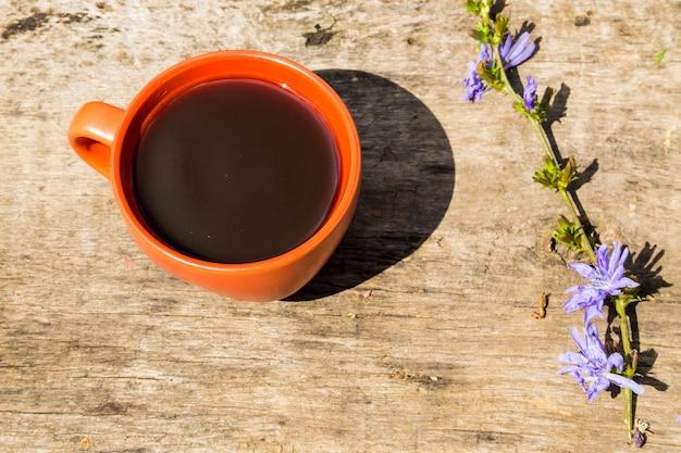 Copo com bebida de chicória e flores de chicória azul em mesa de madeira rústica