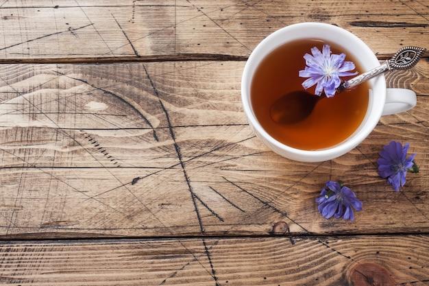 Copo com bebida de chicória e flores de chicória azul na mesa de madeira