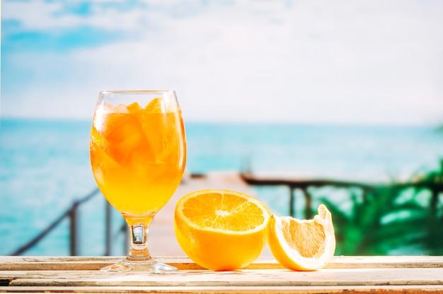 Copo com bebida de laranja e laranja fatiada na mesa de madeira