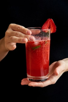 Copo com bebida vermelha. cozinhe em casa coquetel de verão fresco com morangos, limão e hortelã. um bom dia café da manhã saudável bebida batido feito de super alimentos, frutas, bagas