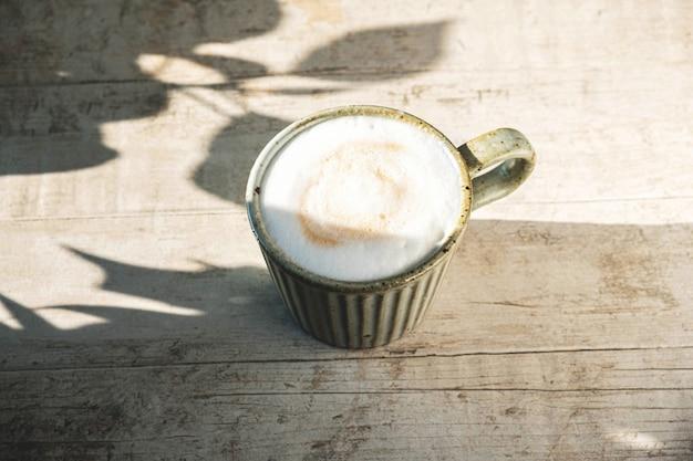 Copo com café cappuccino em uma madeira branca com uma sombra das folhas da árvore.