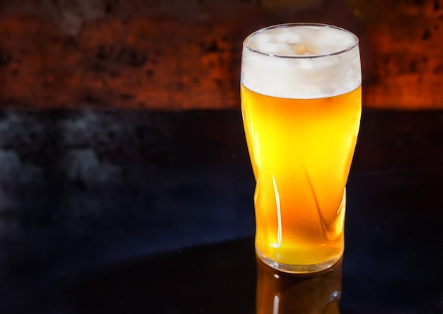 Copo com cerveja light não filtrada recém-derramada em uma superfície de espelho preta. conceito de alimentos e bebidas