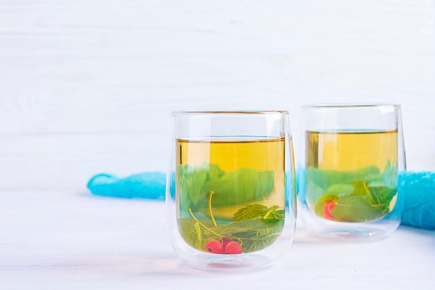 Copo com chá verde de baga e hortelã.