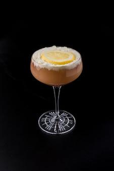 Copo com cocktail vermelho com fatia de creme e laranja em fundo preto