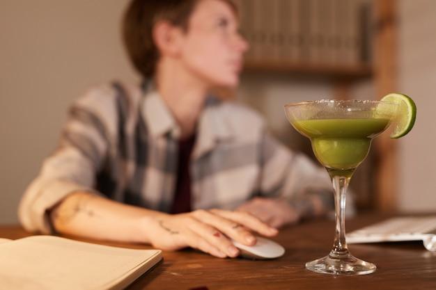 Copo com coquetel de álcool em cima da mesa com uma mulher trabalhando