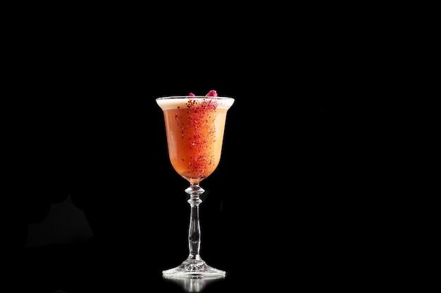 Copo com coquetel de laranja decorado com rosa seca na barra em um fundo preto