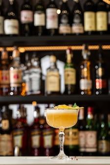 Copo com coquetel de limão amarelo decorado com abacaxi seco e hortelã no balcão do bar desfocado