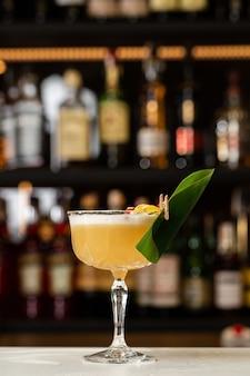 Copo com coquetel de limão amarelo decorado com abacaxi seco e hortelã no fundo do balcão do bar desfocado.
