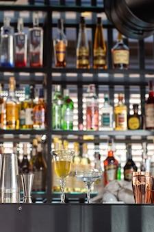 Copo com coquetel de limão amarelo na barra sobre um fundo desfocado onde as bebidas são decoradas