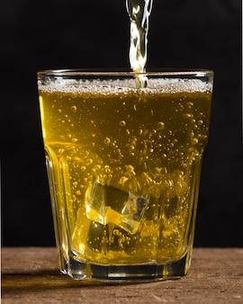 Copo com cubos de gelo e cerveja