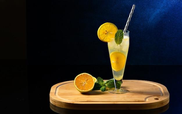 Copo com gelo e laranja decorando em uma placa de madeira sobre fundo escuro bebida ingrediente de preparação