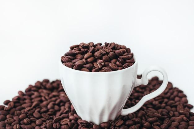 Copo com grãos de café torrados aromáticos frescos isolados no fundo branco cope space