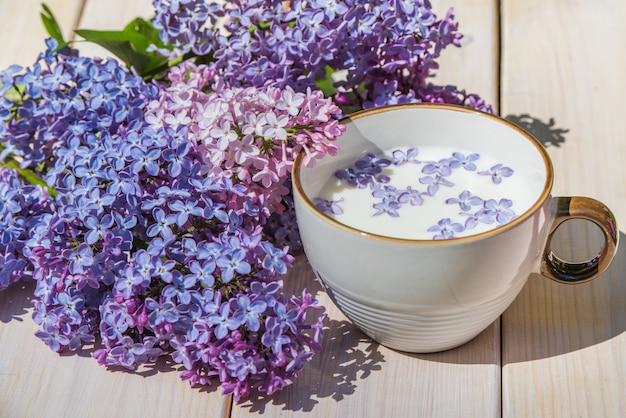 Copo com leite e pequenas flores lilás roxas