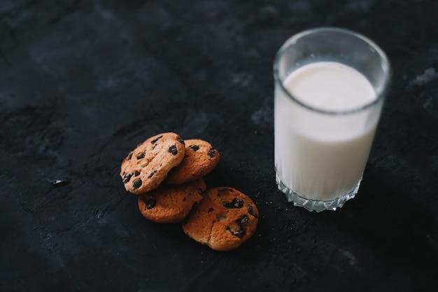Copo com leite fresco e biscoitos de chocolate na superfície escura