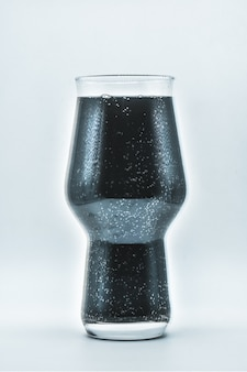 Copo com líquido preto sobre fundo branco, copo com vinho escuro