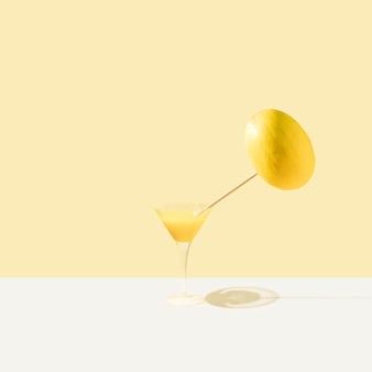 Copo com refresco amarelo e melão vibrante em fundo bege e branco pastel. conceito de comida mínima. ideia de primavera ou verão.