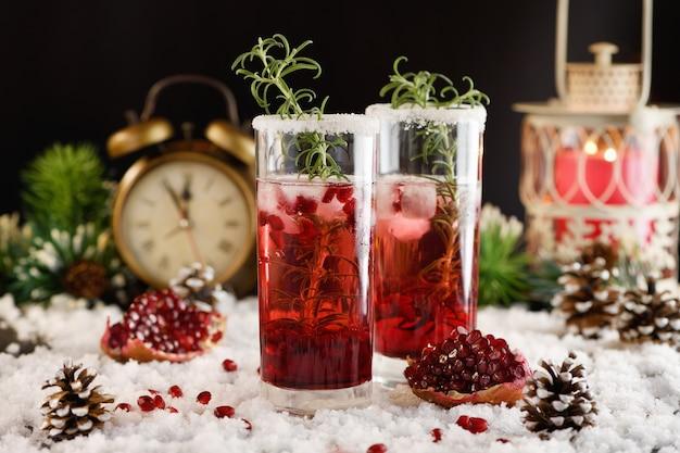 Copo com romã margarita com cranberries cristalizadas, alecrim. coquetel perfeito para uma festa de natal