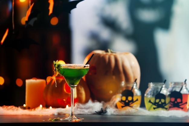 Copo com saboroso coquetel para festa de halloween, no fundo desfocado