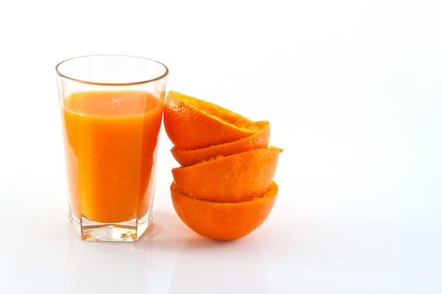 Copo com suco de laranja delicioso e laranjas espremidas