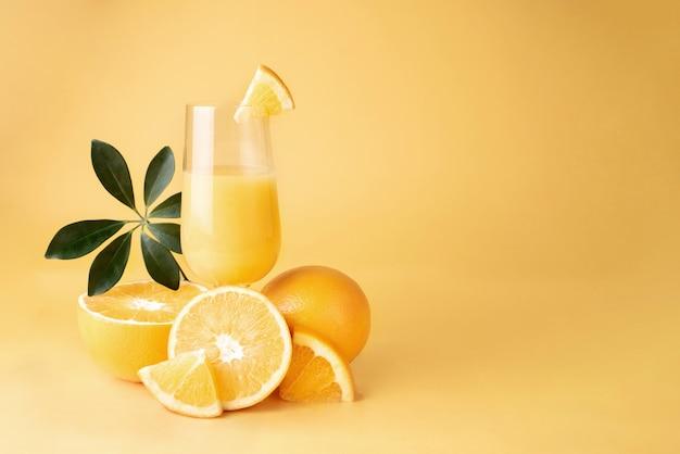 Copo com suco de laranja fresco e corte ao meio as laranjas.