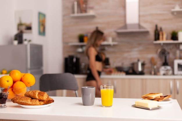 Copo com suco de laranja fresco na cozinha durante o café da manhã com a dona de casa sexy no fundo