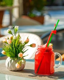 Copo com suco de melancia frio e um vaso de flores