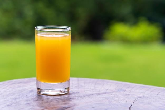 Copo com suco tropical de manga e maracujá na mesa de madeira no quintal, close-up, tanzânia, áfrica oriental, copie o espaço
