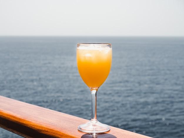 Copo com um cocktail e cubos de gelo
