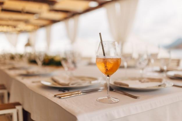 Copo com um coquetel de laranja com gelo e um tubo na mesa do banquete