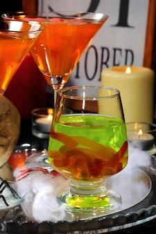 Copo com uma bebida verde com minhocas na mesa em homenagem ao halloween entre outros coquetéis