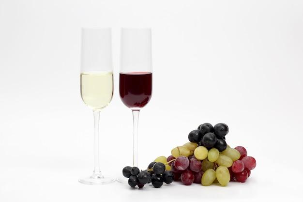 Copo com vinho tinto e branco com uvas em um fundo claro