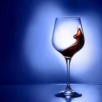 Copo com vinho tinto em um fundo azul com espaço de cópia. salpicos de vinho em uma taça.