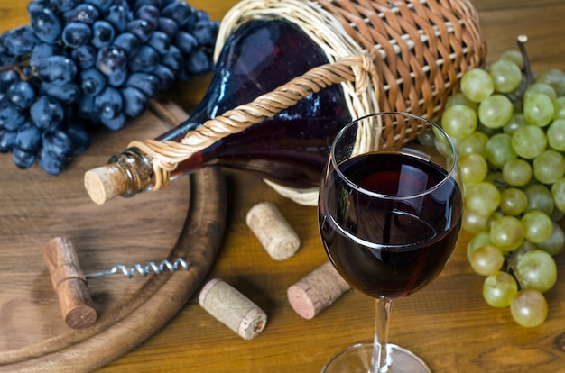 Copo com vinho tinto, garrafa, cacho de uvas, saca-rolhas e cortiça em uma mesa de madeira. vista de cima, estilo rústico.