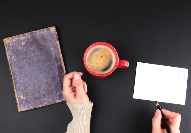 Copo creameric vermelho com café preto, mãos femininas