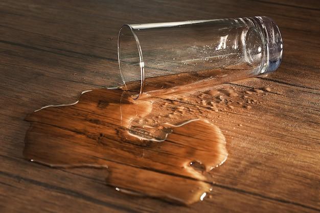 Copo d'água derramado no espaço de madeira