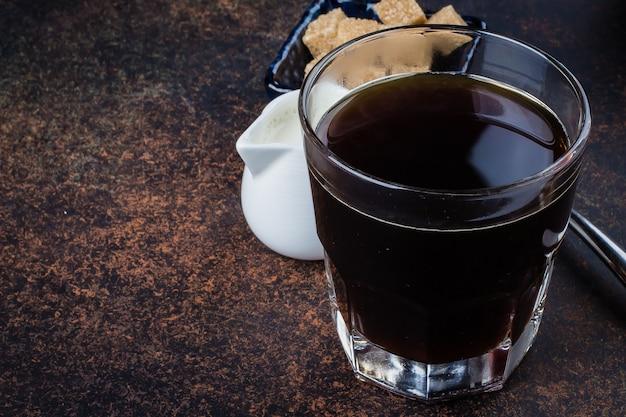 Copo da manhã do café quente com leite e açúcar na tabela concreta de pedra escura do fundo. espaço da cópia