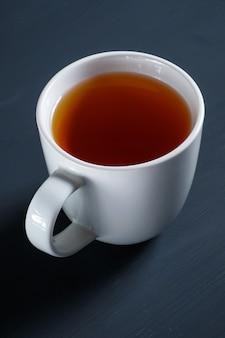 Copo da vista superior do chá na tabela de madeira preta.
