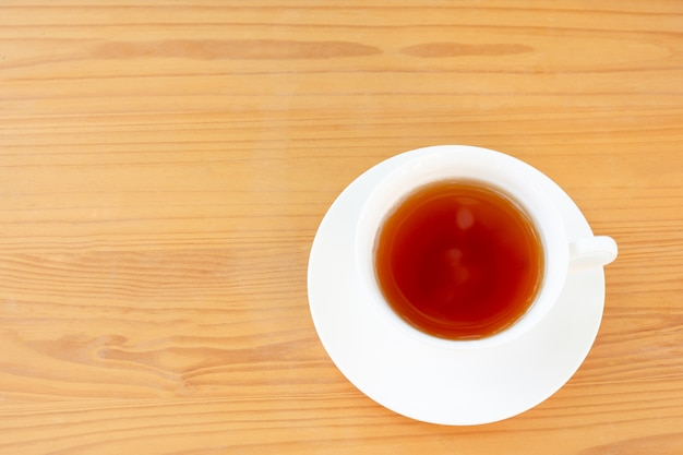 Copo da vista superior do chá na tabela de madeira.